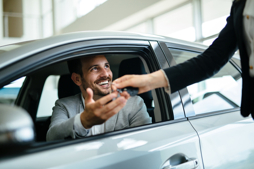 Portrait of happy young customer buying new car
